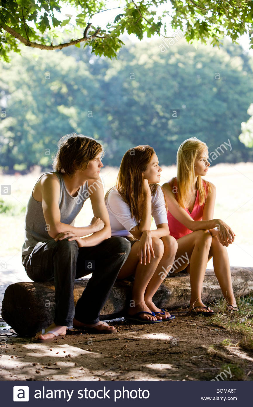 Three young people sitting on a log, in a park - Stock Image