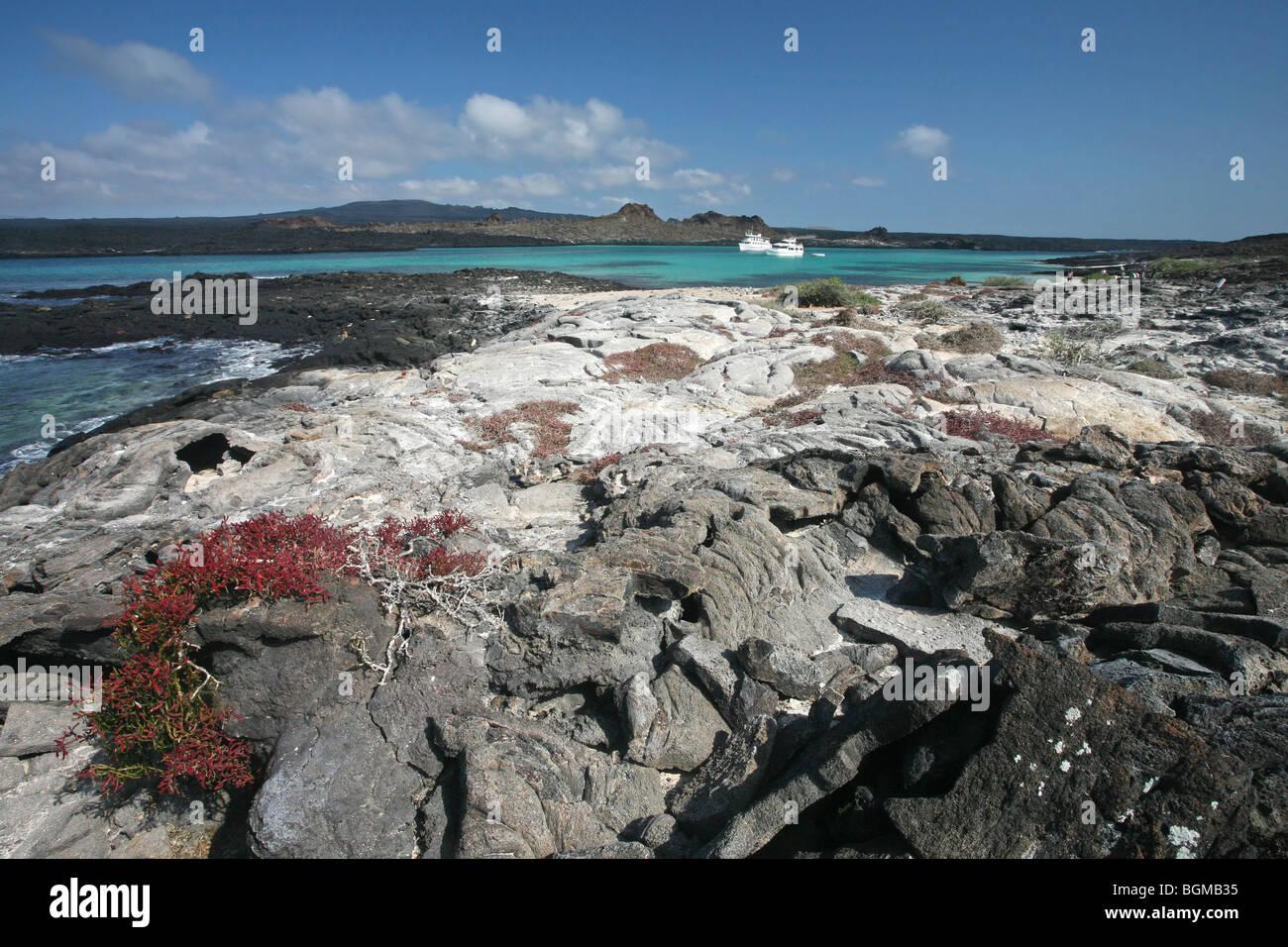 Boats in bay and lava field at Sombrero Chino / Chinaman's Hat on Santiago Island / San Salvador Island, Galápagos - Stock Image