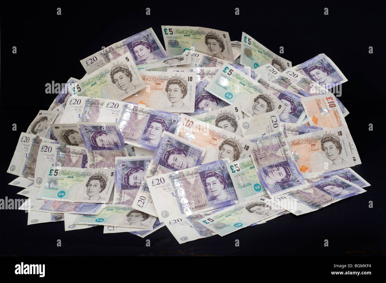 A pile of assorted banknotes in £5 £10 and £20 denominations - Stock Image