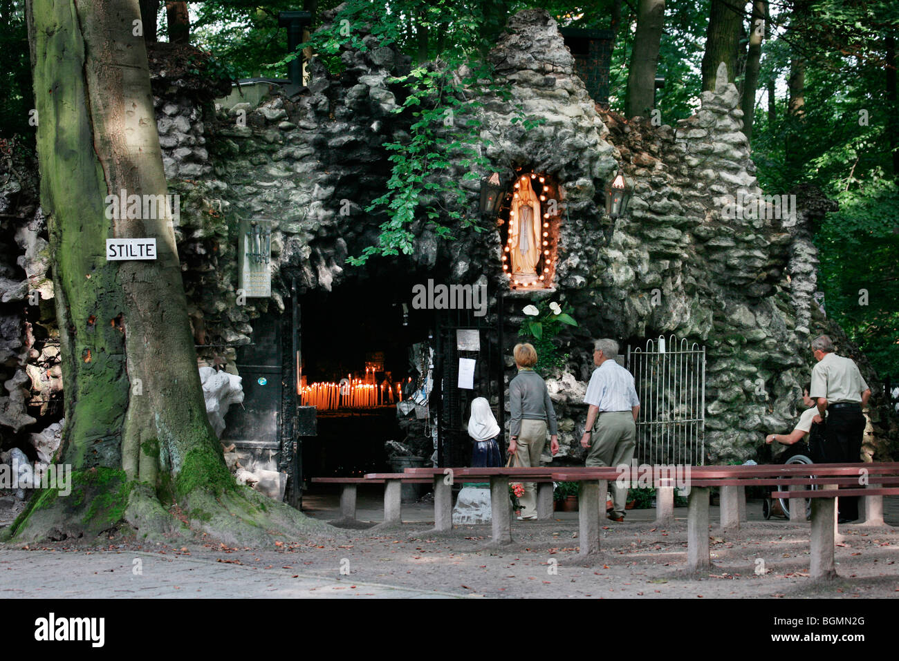 People praying at the Lourdes grotto, Oostakker-Lourdes place of pilgrimage near Ghent, East Flanders, Belgium - Stock Image