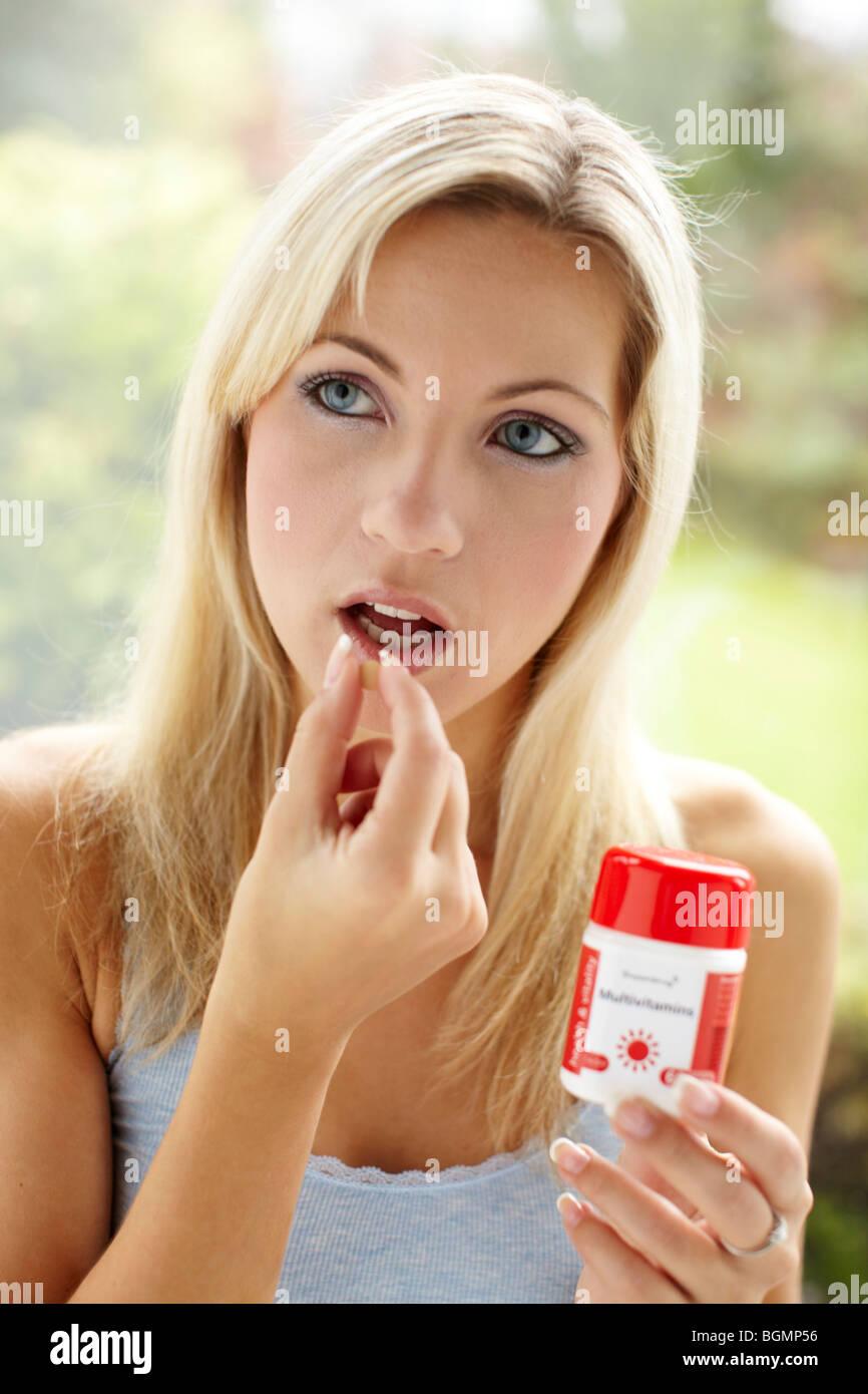 Girl taking vitamin tablets - Stock Image