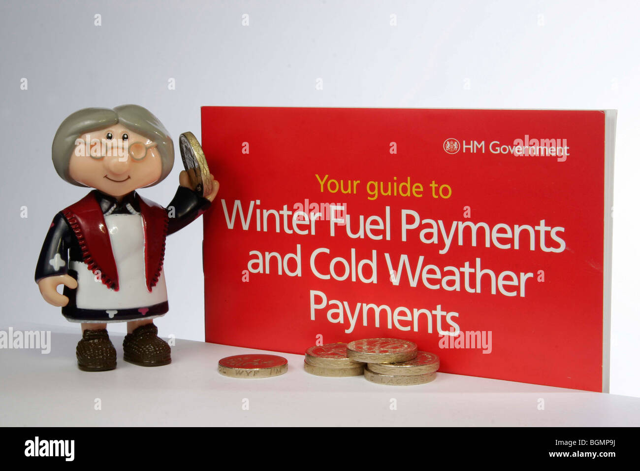 Model of old lady holding money next to a government leaflet for winter fuel and cold weather payments - Stock Image