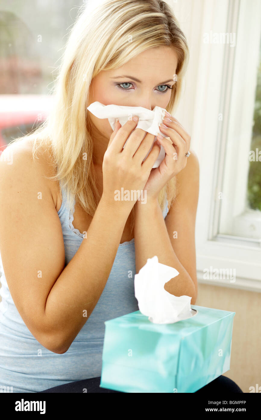 Girl with cold blowing nose - Stock Image