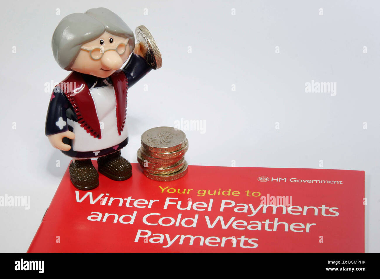 Model of old lady holding money next to a government leaflet for winter fuel and cold weather payments Stock Photo