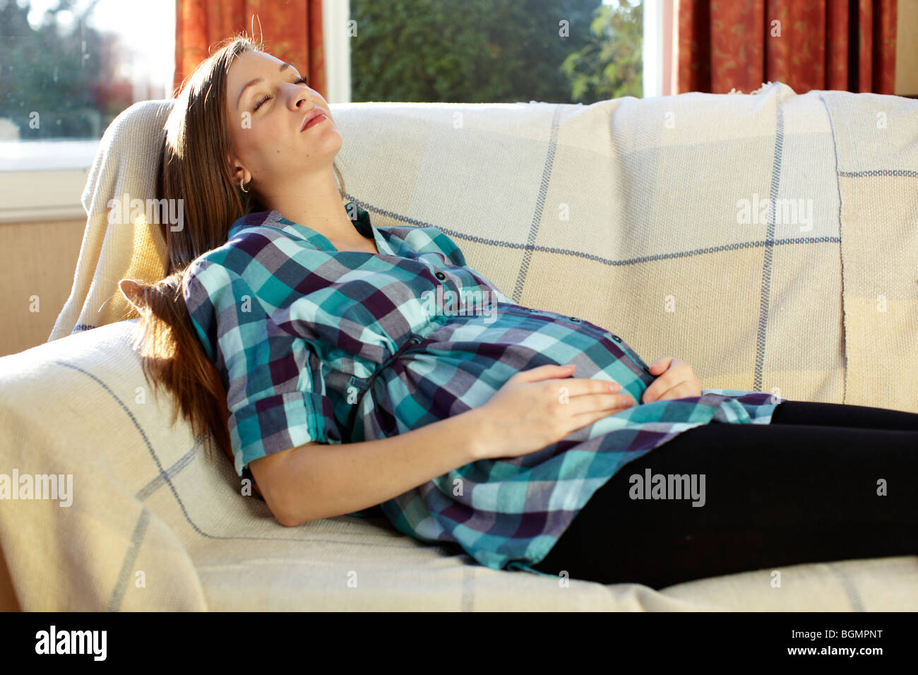 Pregnant woman reading leaflets - Stock Image