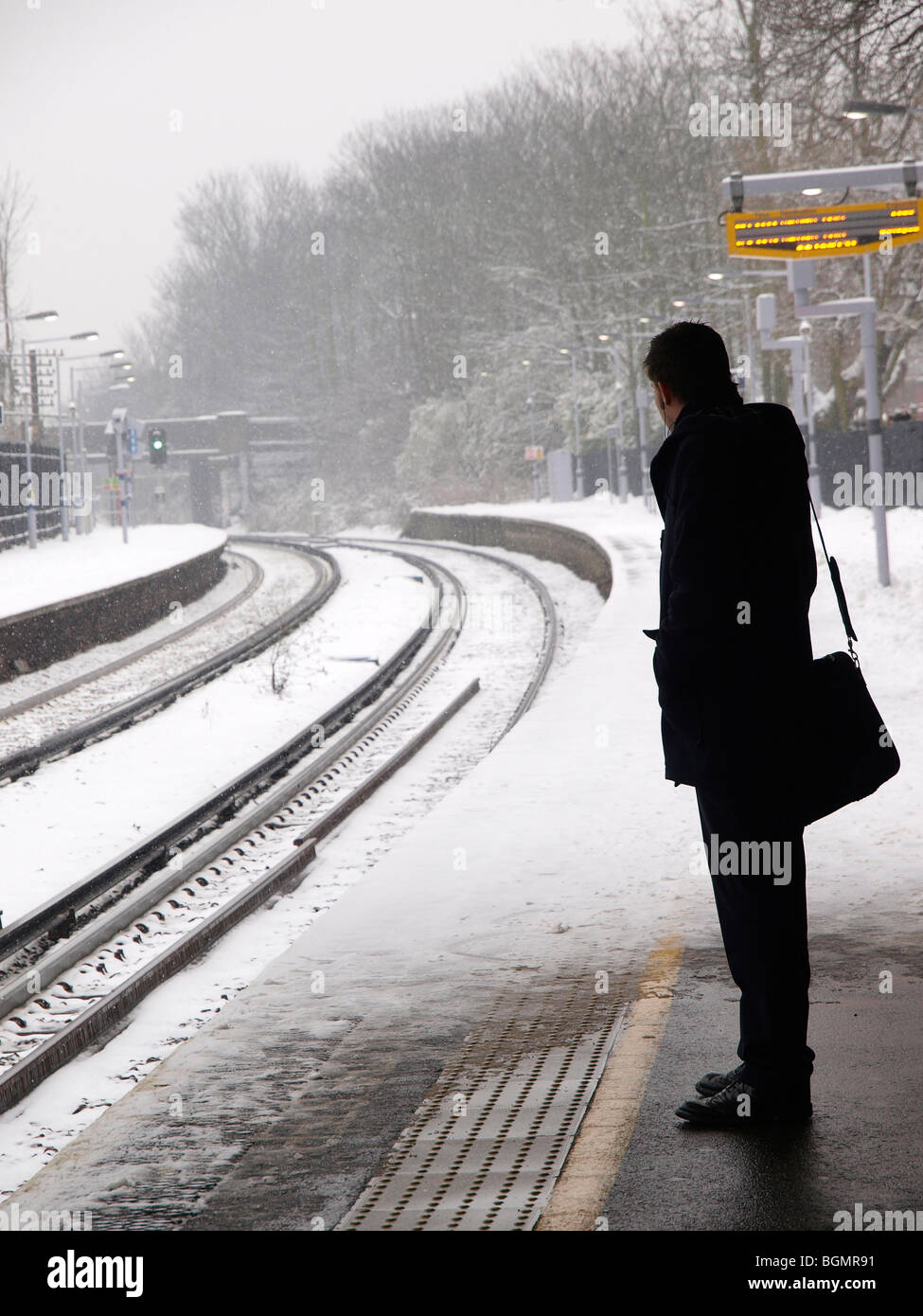 Commuter waiting for a  train delayed by snow at a suburban railway station outside London. - Stock Image