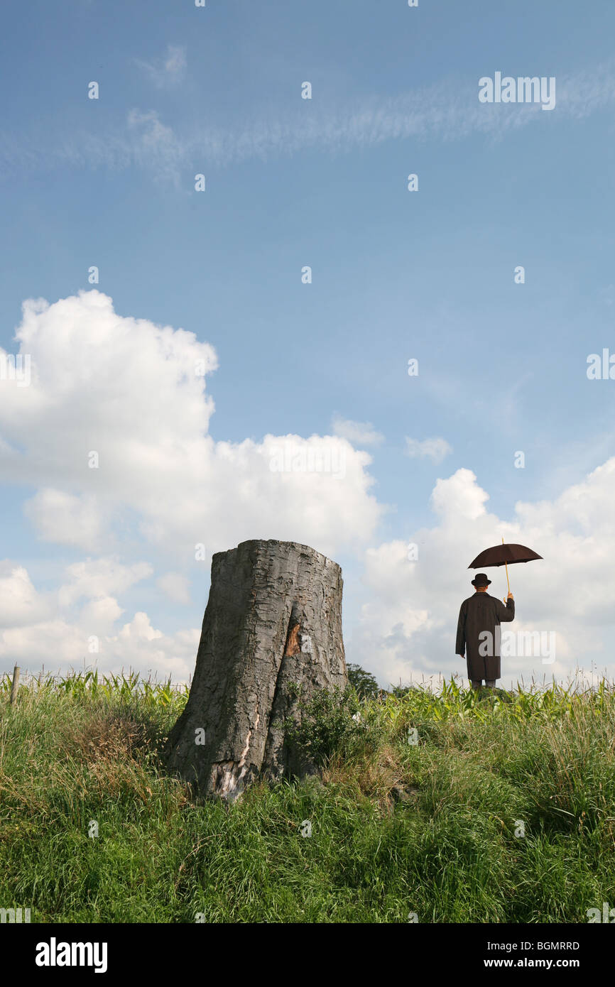 man stands holding umbrella near tree stump with blue sky and clouds - Stock Image