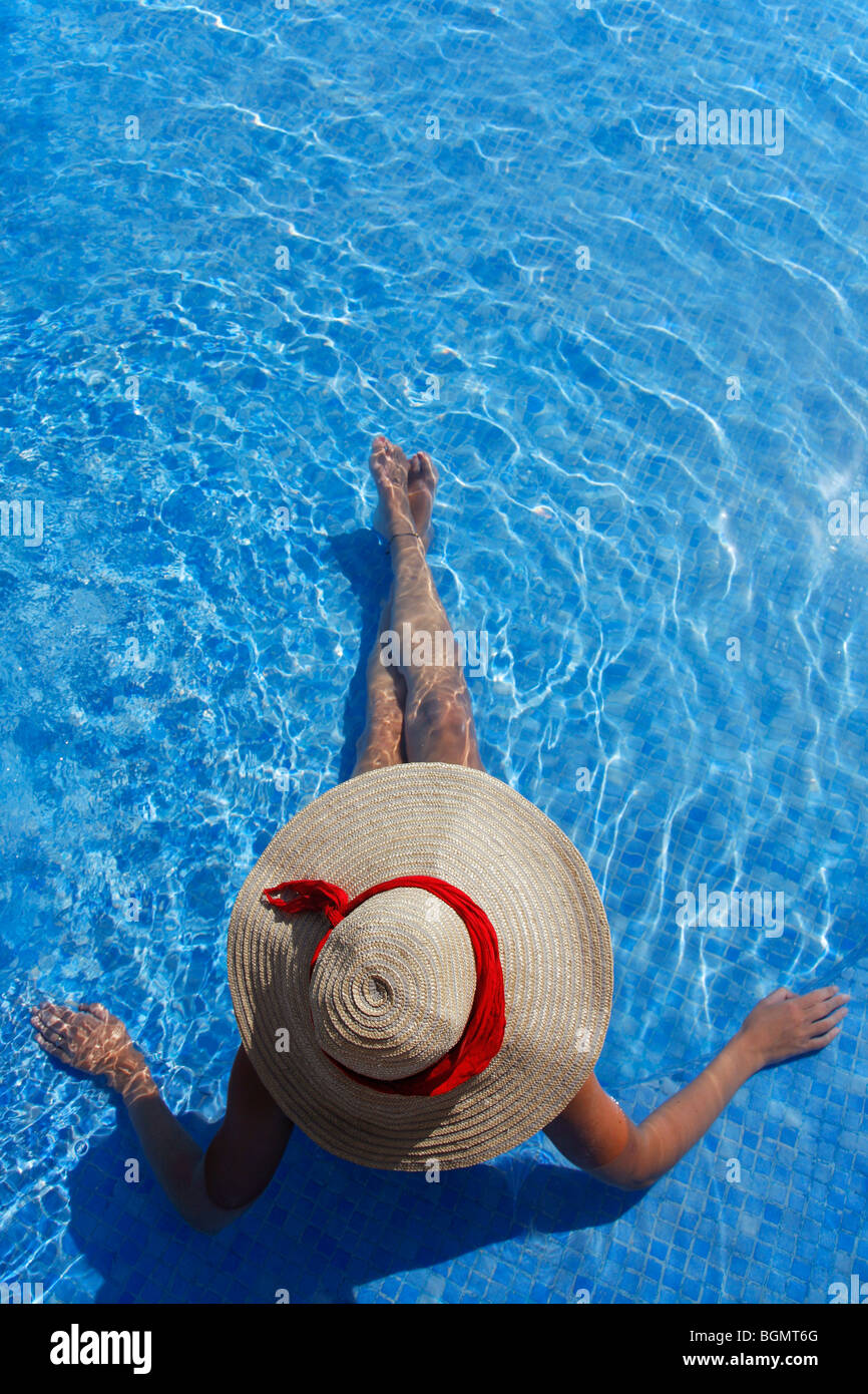 Woman in a sun hat sunbathing in a blue swimming pool - Stock Image