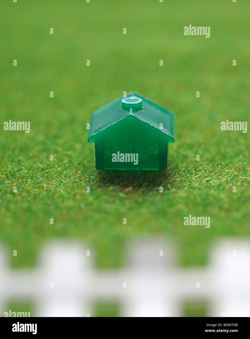Monopoly house on green grass with white picket fence. - Stock Image
