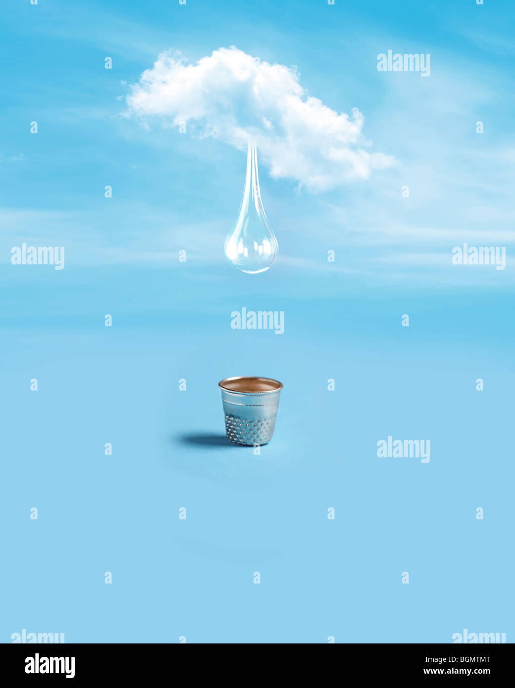 single drop of water falls from a lone cloud into a small silver thimble - Stock Image