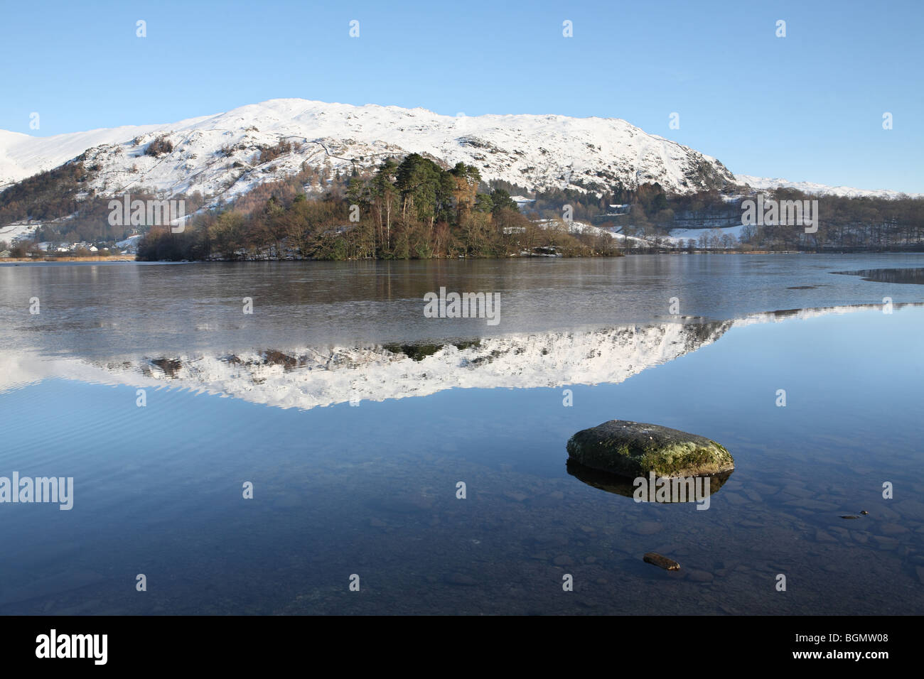 Grasmere with snow clad mountains reflected in the lake, Cumbria, UK - Stock Image