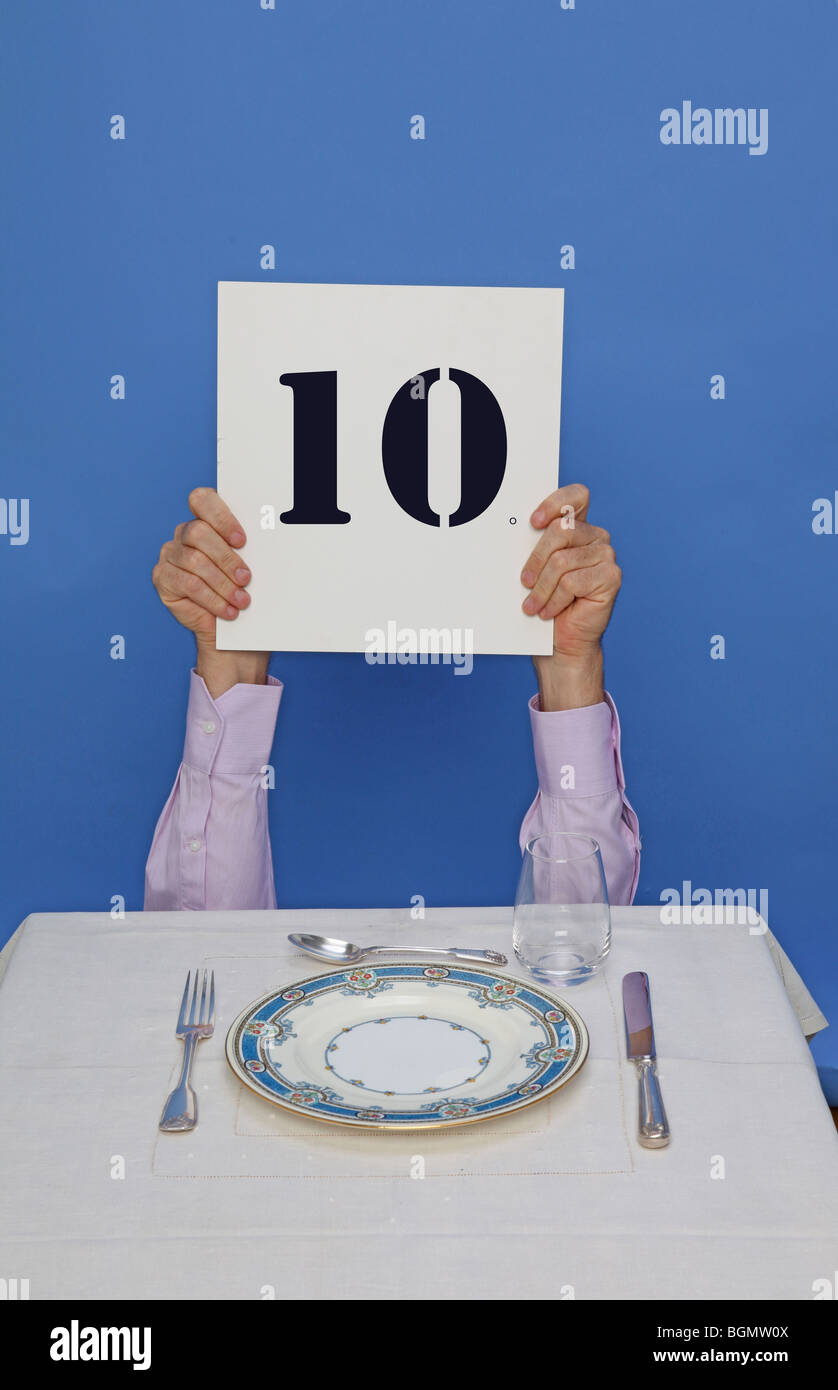 man eating at table holds up 10 sign to rate dinner - Stock Image