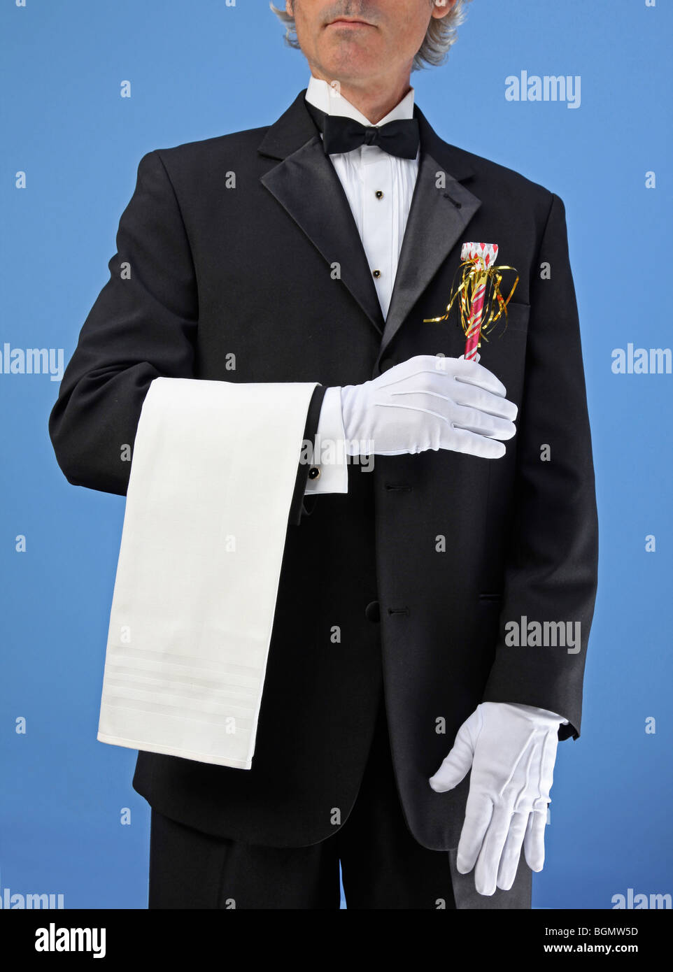 butler or waiter stands with party blower in hand - Stock Image