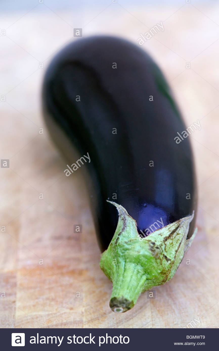 Aubergine (eggplant) on chopping board - Stock Image