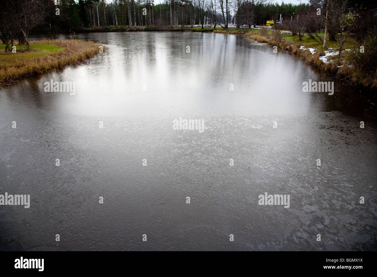 Thin ice cover on a frozen garden pond , Finland - Stock Image