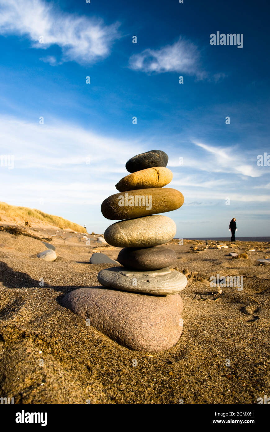 A stone tower built on the beach at Spurn Point, the old lighthouse visible in the background - Stock Image