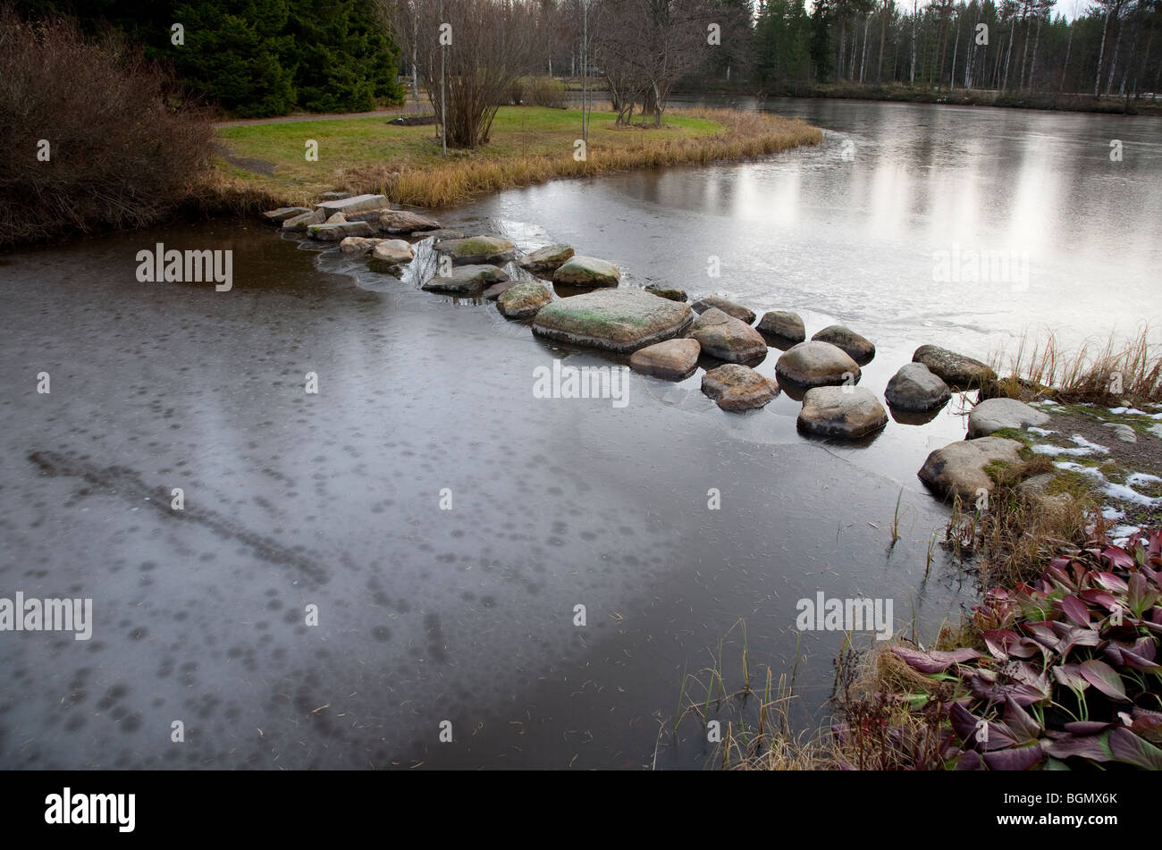 Stepping stones over a frozen garden pond , Finland - Stock Image
