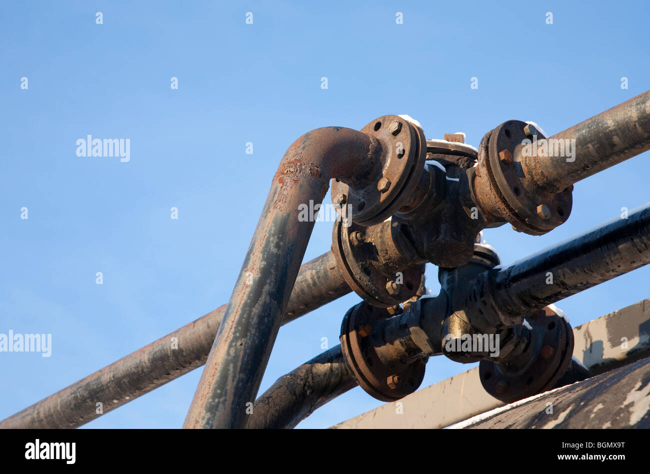 Pipe joint against blue sky - Stock Image
