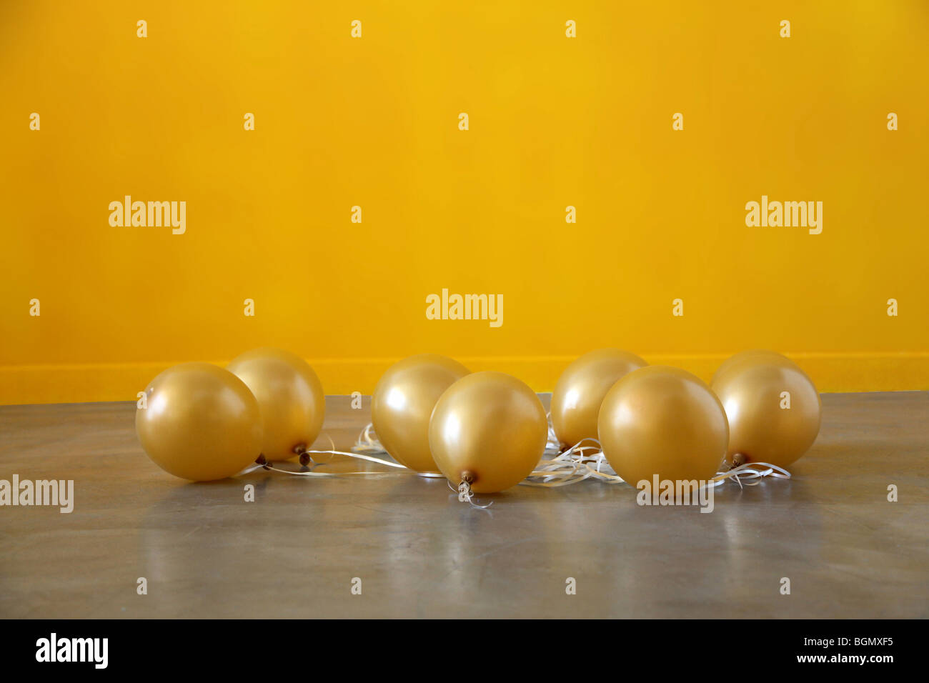 gold balloons sink to the floor after the party deflated - Stock Image