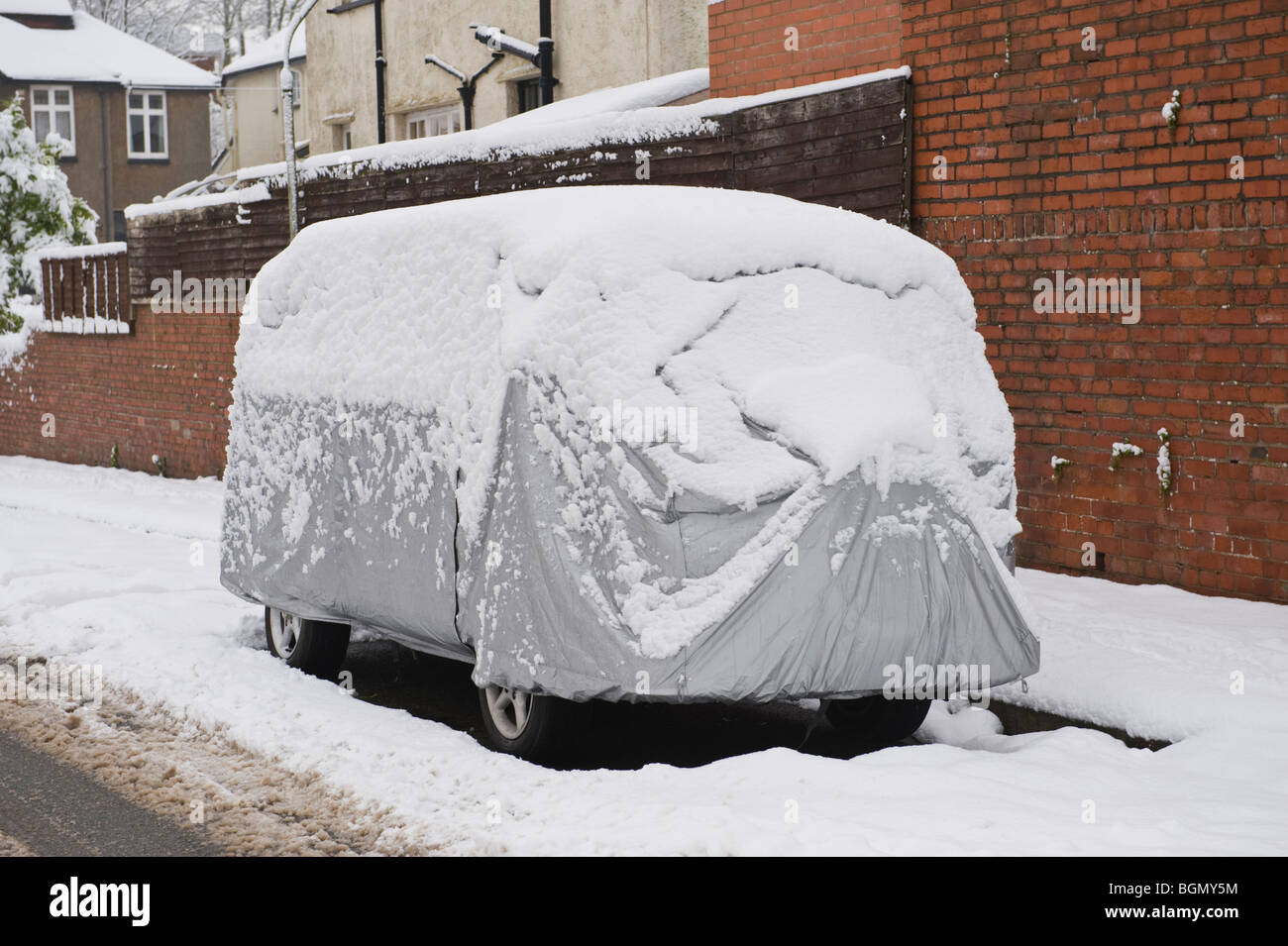 VW camper van with protective cover covered in snow at Newport South Wales UK - Stock Image