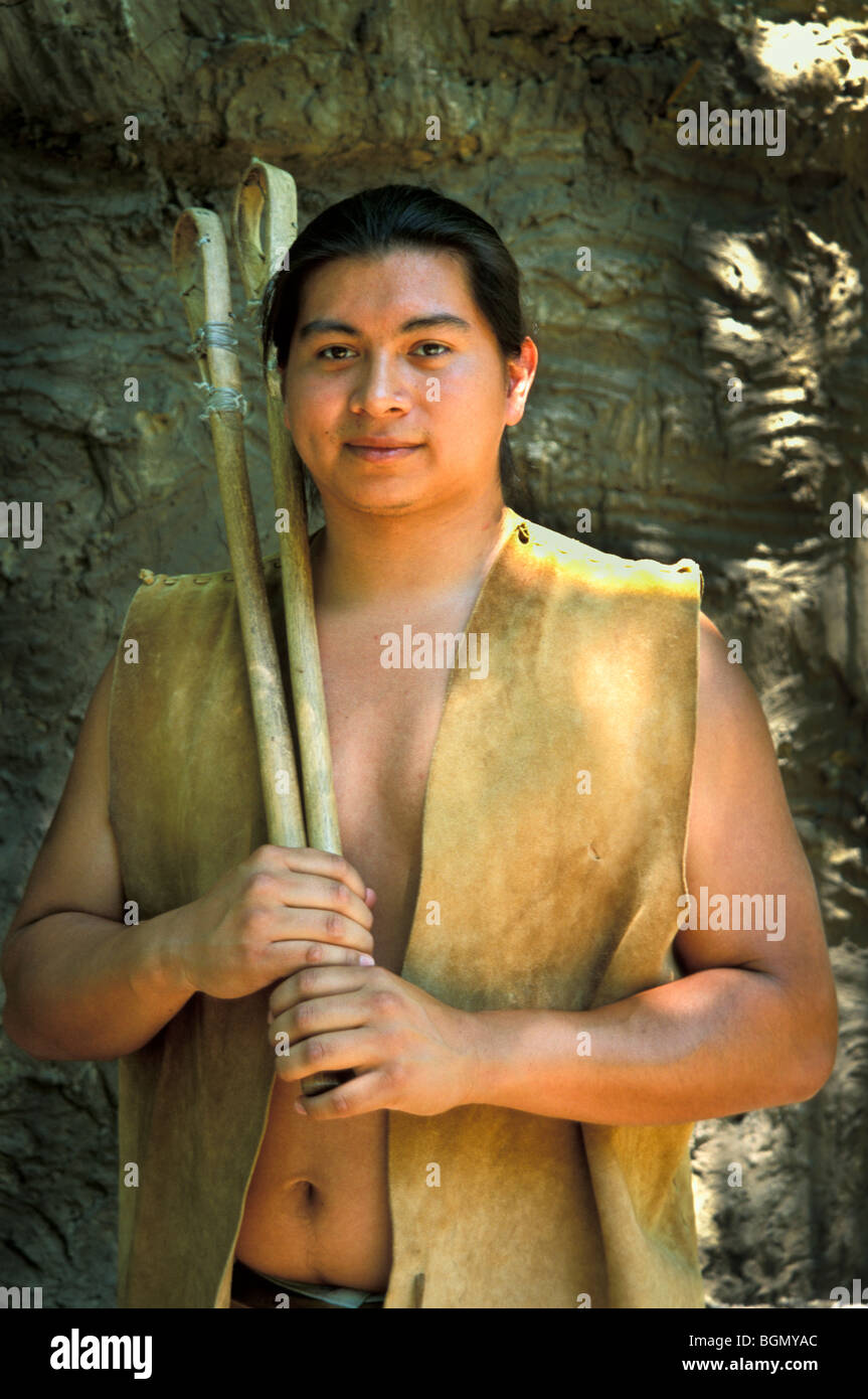 Cherokee man dressed in traditional deerhide clothing holds a pair of stickball game sticks, Tahlequay OK. Stock Photo