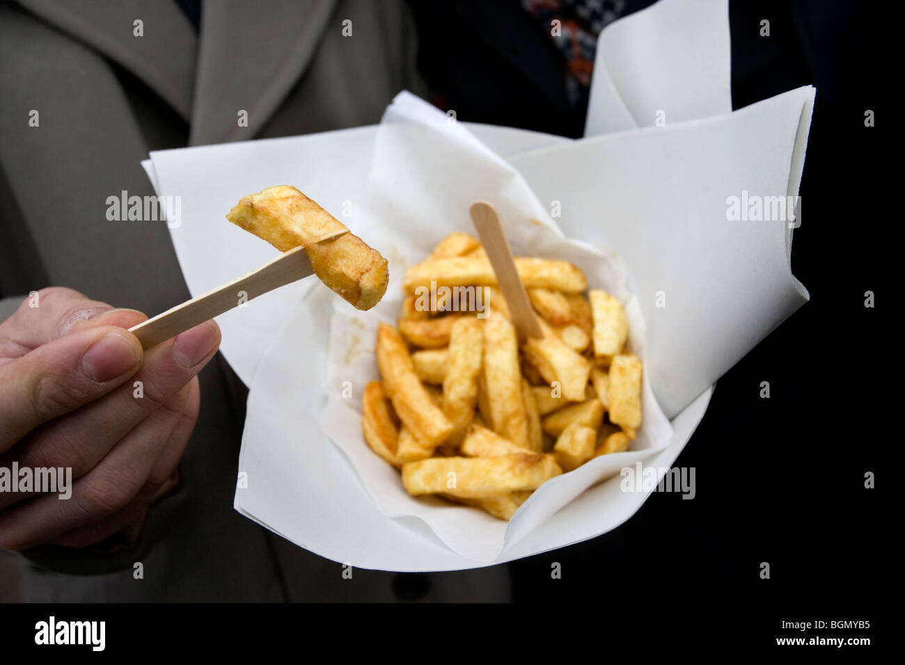 A young couple enjoy a small portion of chips outside Bankers Traditional Fish and Chip restaurant and take-away, - Stock Image