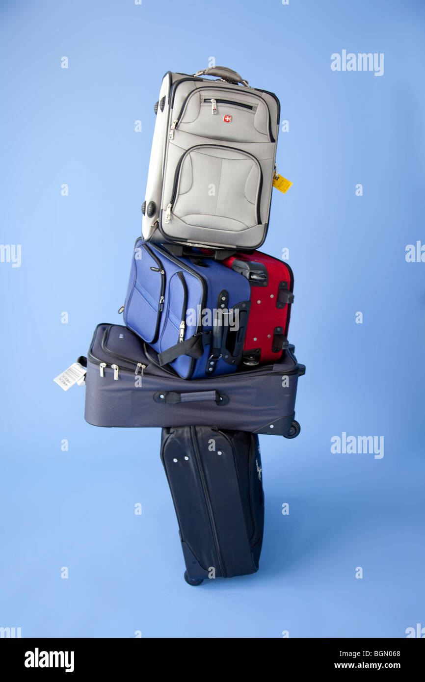 five stacked up suitcases with tags ready to check. - Stock Image