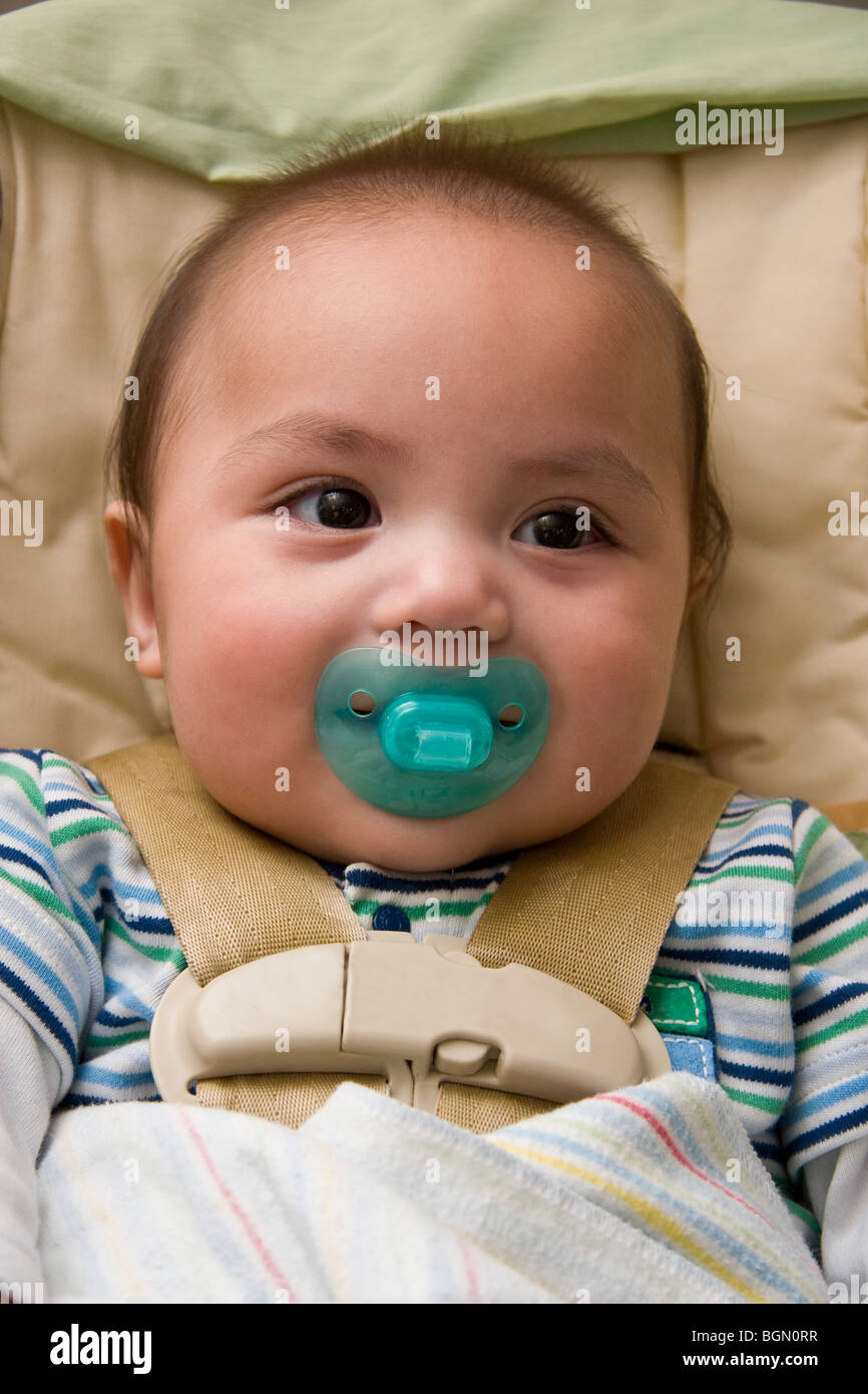 Healthy Native American infant sucking on a pacifier happily sits inside his car seat Stock Photo