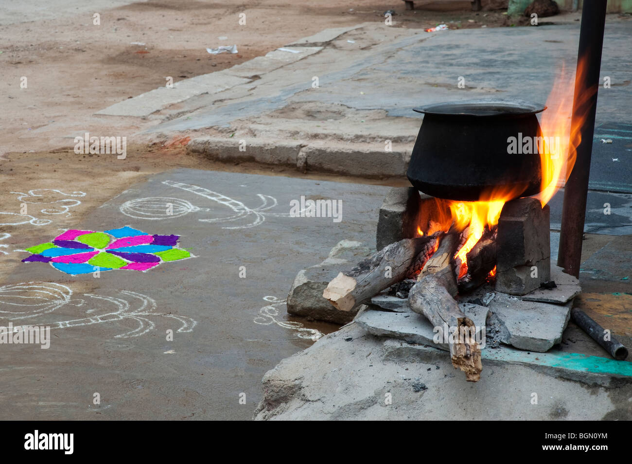 Boiling water on an open fire in a rural Indian village in front of a Rangoli design during the festival of sankranthi. - Stock Image
