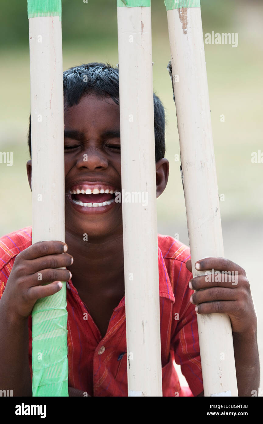 Indian boys face behind cricket stumps. India - Stock Image