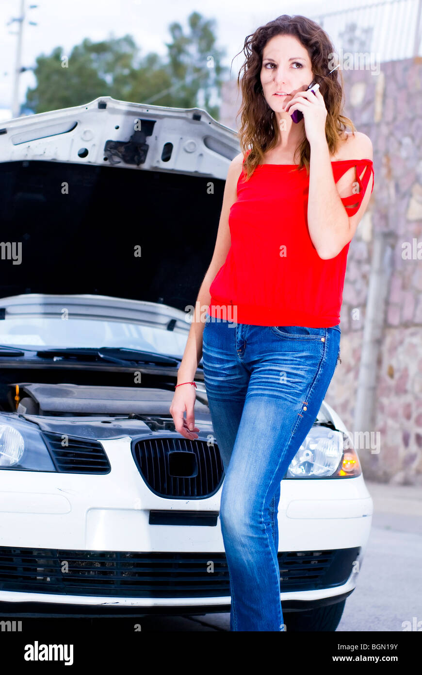 woman calling insurance for car engine breakdown - Stock Image