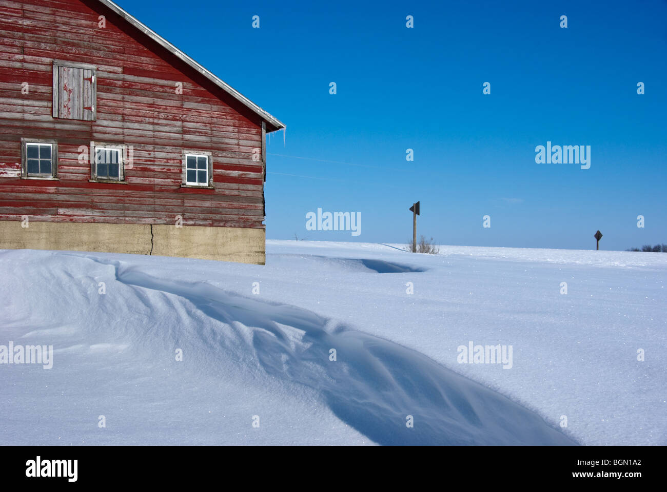A textured snowdrift and an old red barn against a blue sky - Stock Image