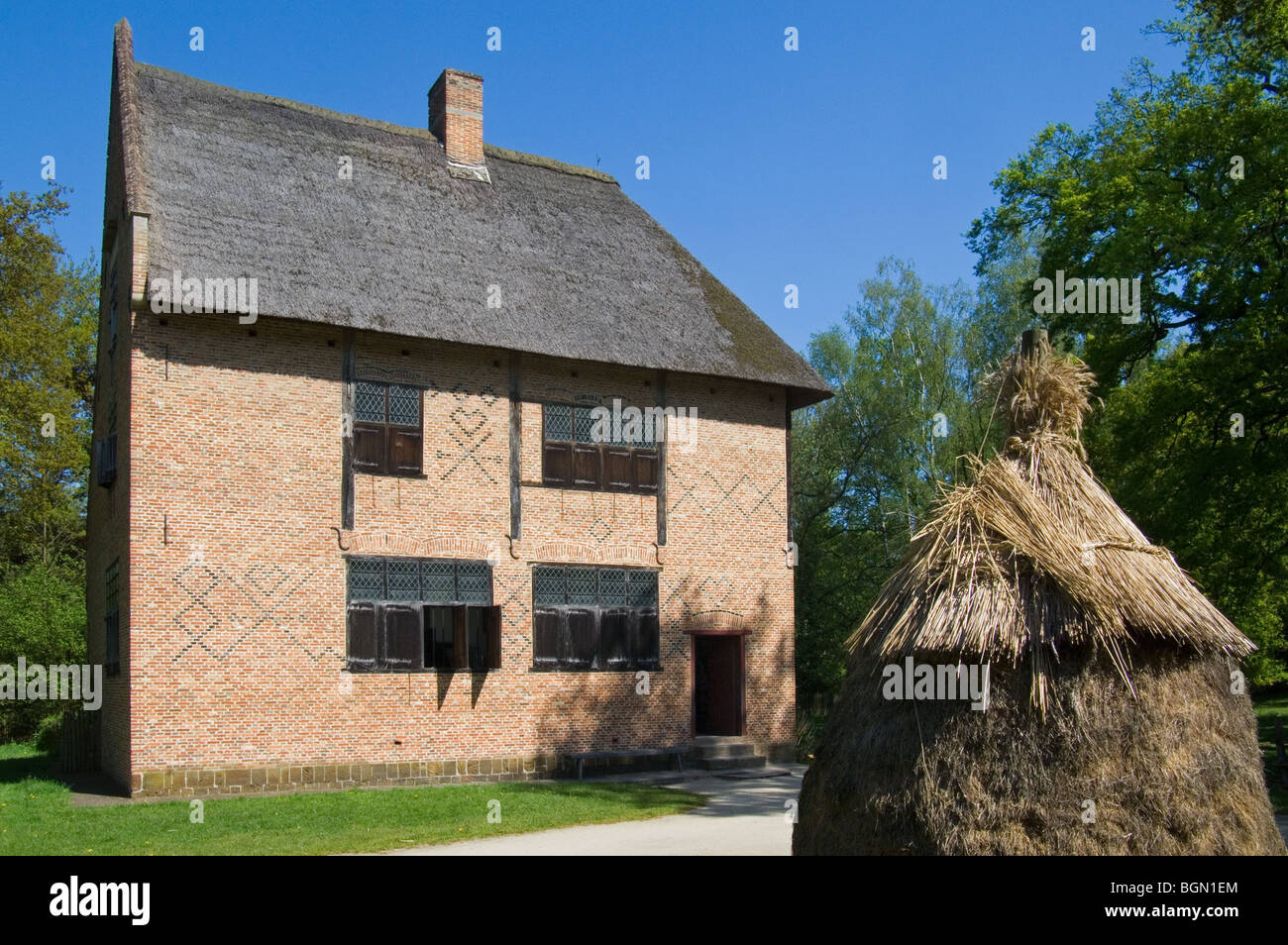 Haystack and traditional brick house in the open air museum Bokrijk, Belgium - Stock Image
