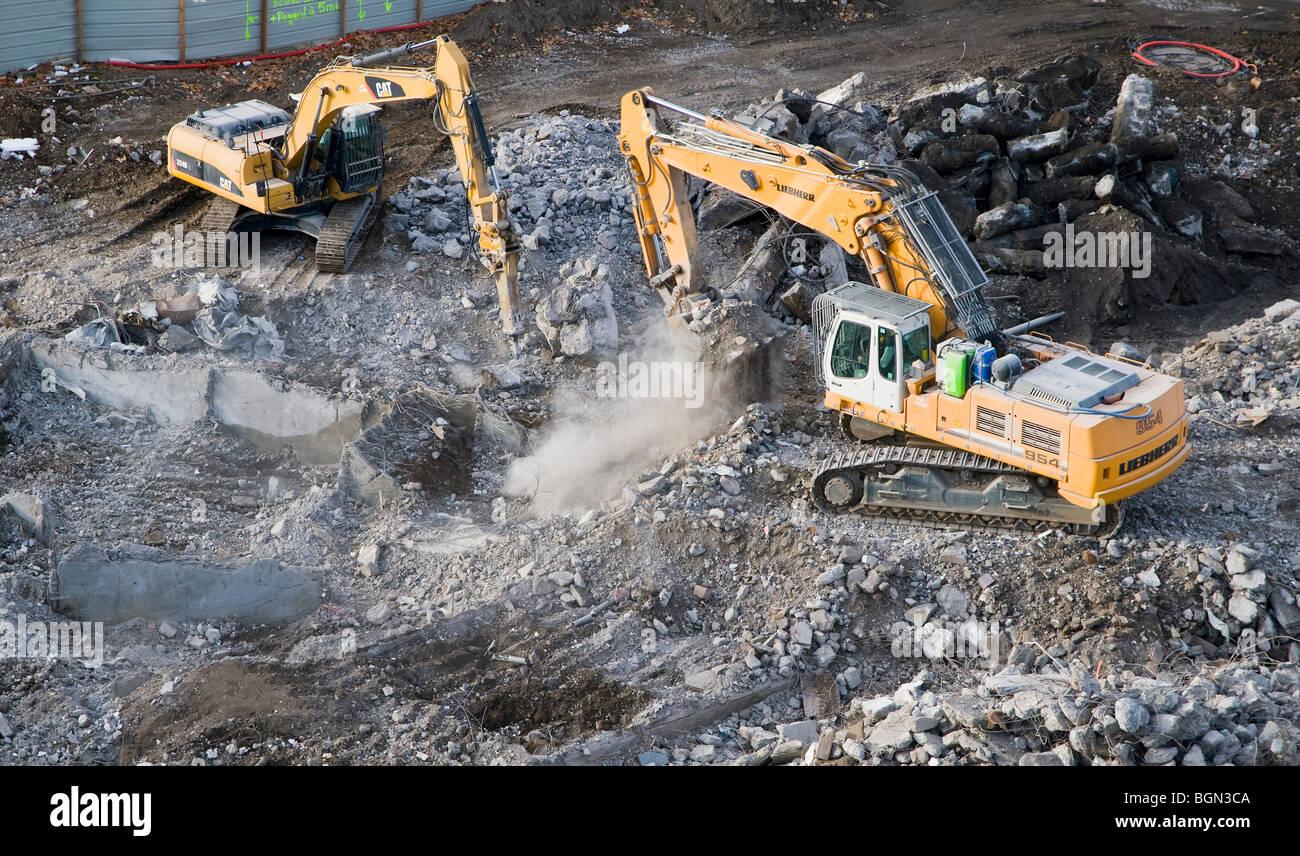 Crawler excavators on a building demolition yard - Stock Image