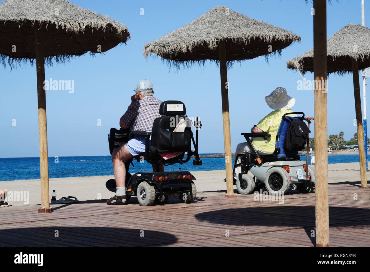 Couple on mobility scooters looking out to sea from Los Cristianos beach on Tenerife in The Canary Islands - Stock Image