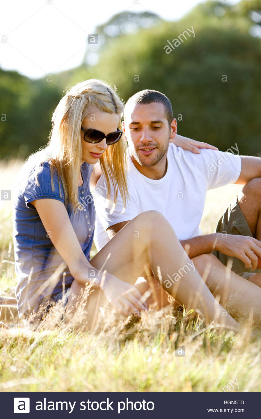 A young couple sitting on the grass in summertime - Stock Image