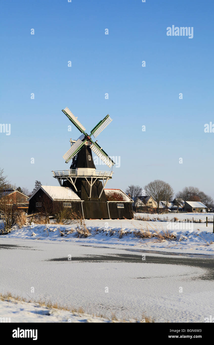 Antique wood and grain mill from 1903 (renovated in 1985) in Ten Boer, The Netherlands near a frozen river - Stock Image