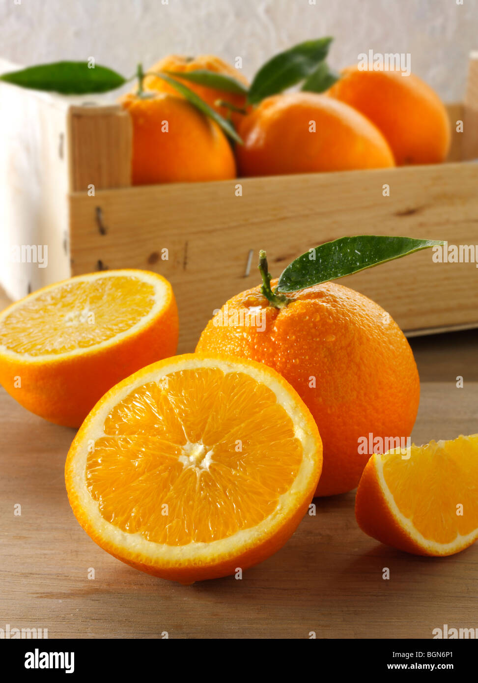 Fresh oranges whole and cut halves with leaves in a box - Stock Image