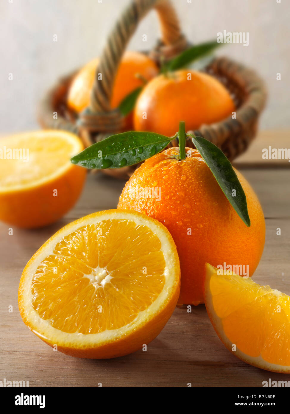 Fresh oranges whole and cut halves with leaves in a kitchen setting - Stock Image