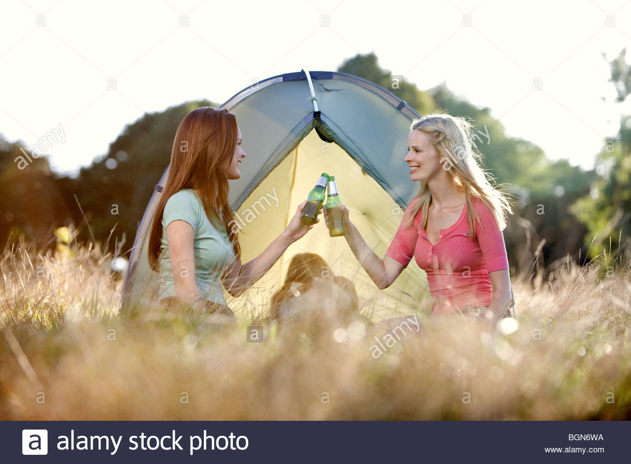 Three young women camping, two drinking beers - Stock Image
