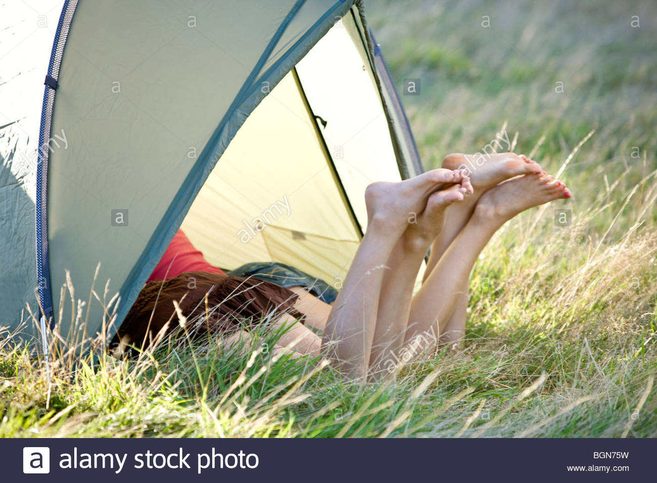 Two young women with their legs sticking out of a tent - Stock Image