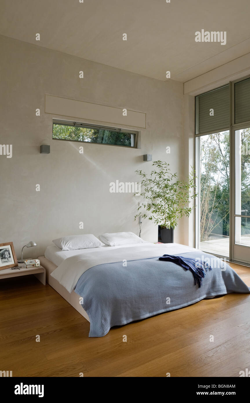 Bedroom with wooden floor in contemporary house - Stock Image