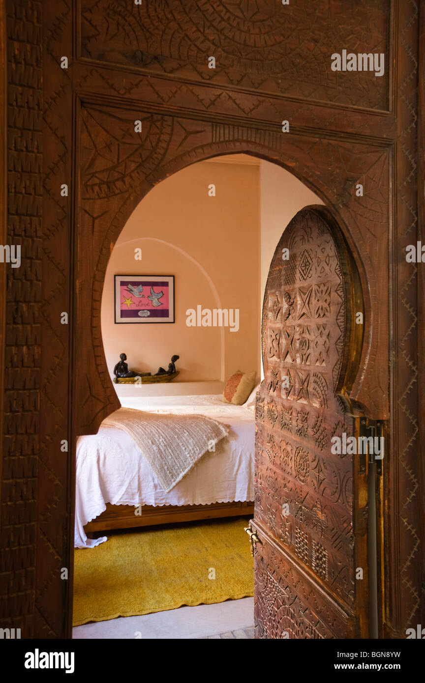Carved doorway opens to bedroom of a riad in the Medina of Marrakesh Stock Photo