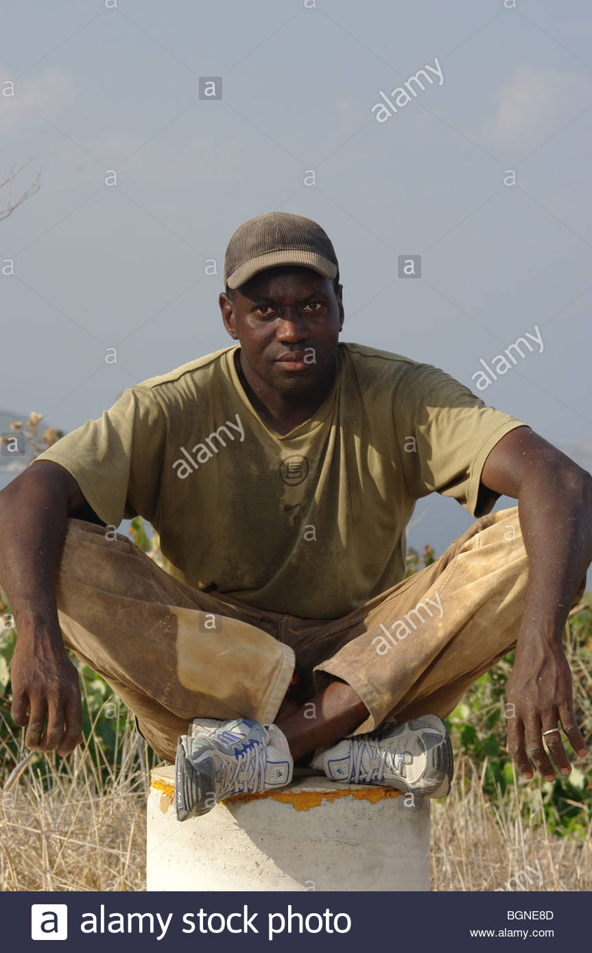 Izza, a 31 year old migrant worker from Senegal, Africa poses in Greece. - Stock Image