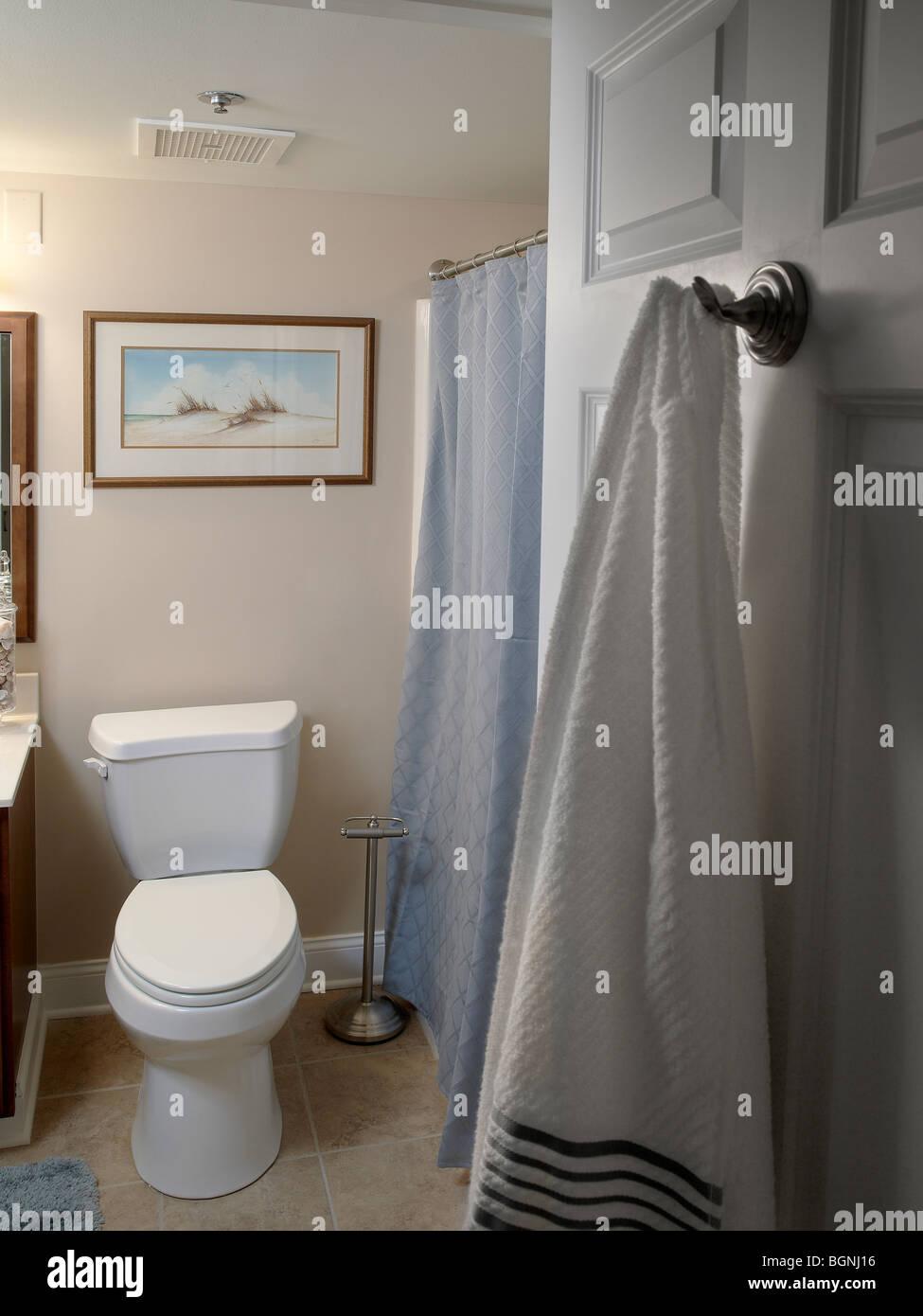 Bathroom With Towel Hanging On Door - Stock Image