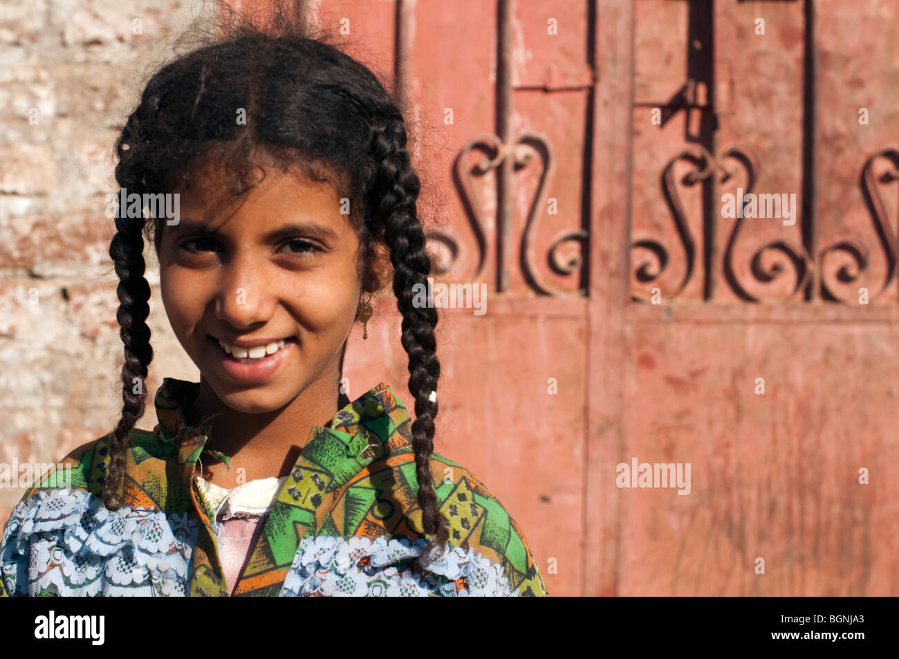 Young Egyptian schoolgirl posing in front of an iron gate that mirrors her braids. - Stock Image