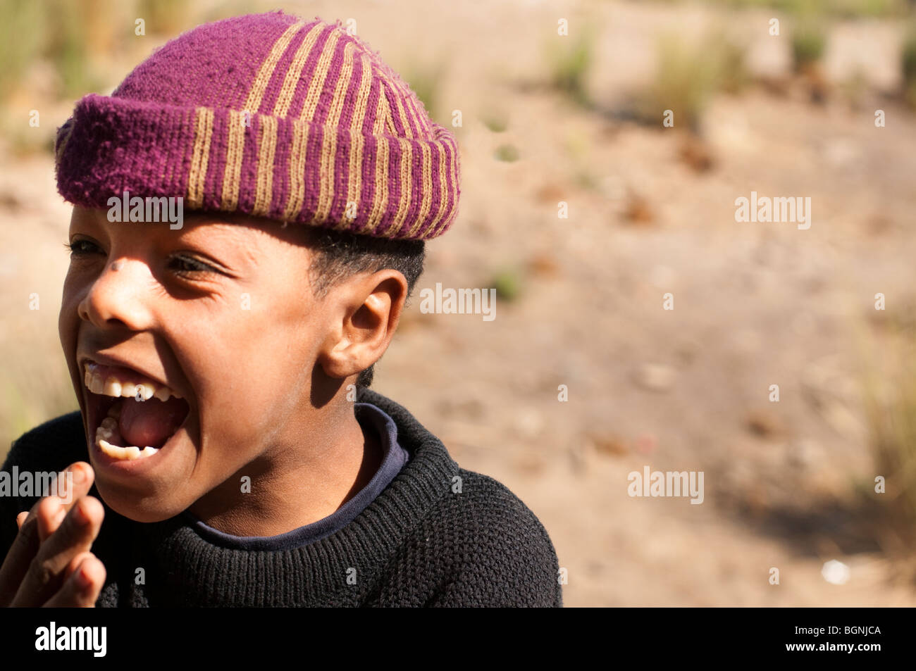 Egyptian youth with striped cap laughing - Stock Image