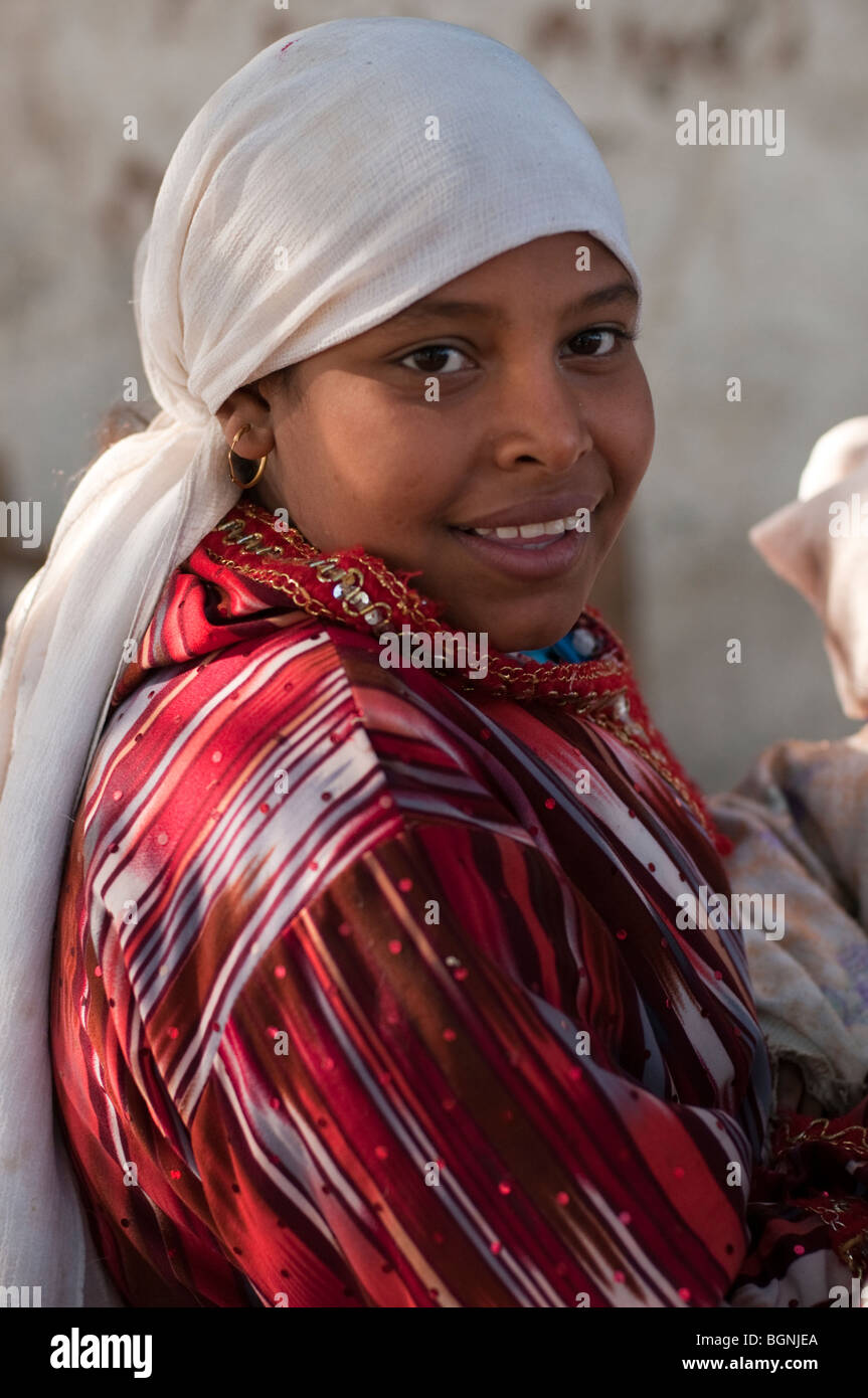 Smiling young Egyptian girl with almond eyes, headscarf and pierced ears. - Stock Image