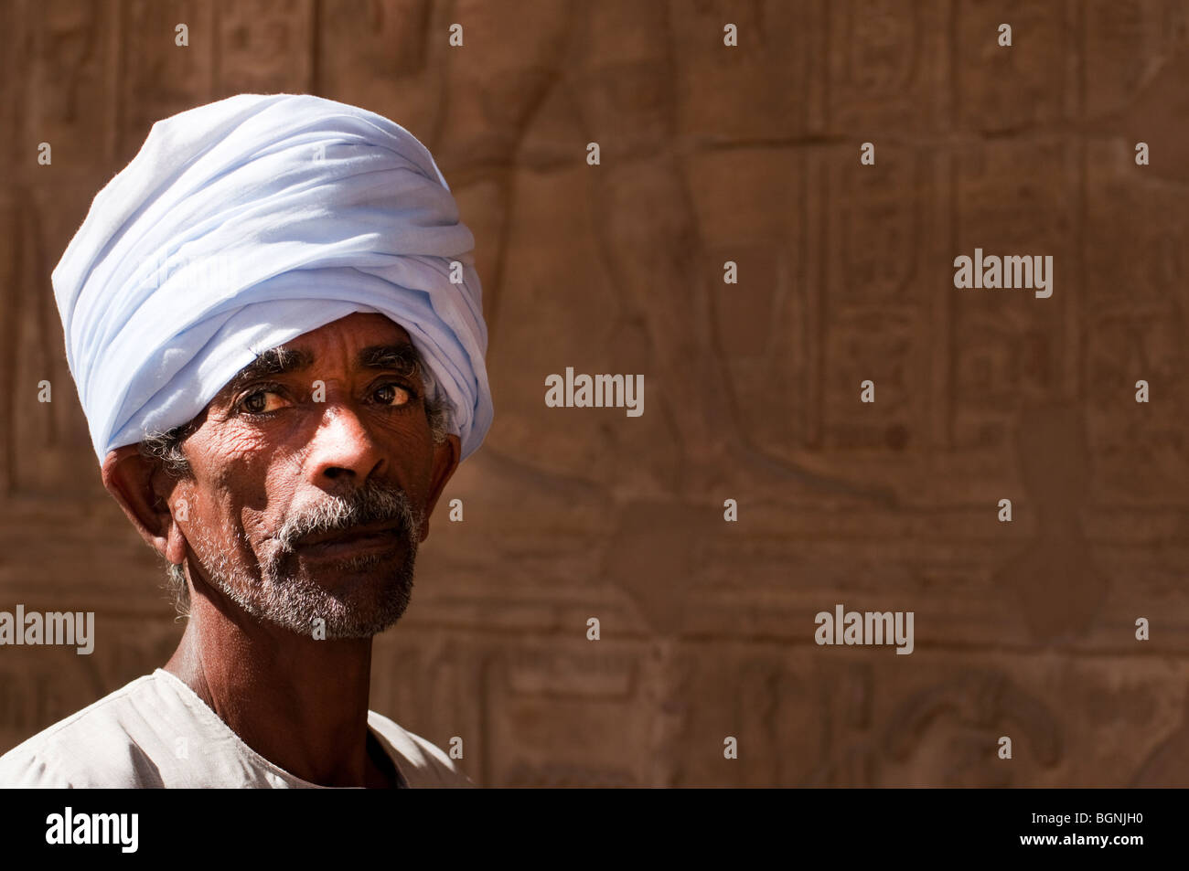 Older Egyptian male in white turban with hieroglyphics behind him - Stock Image