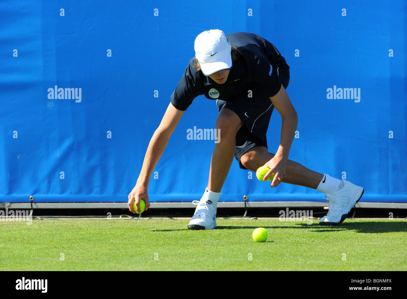A ball boy collects balls ath the end of a game during the Aegon International 2009 Tennis Championships at Devonshire - Stock Image